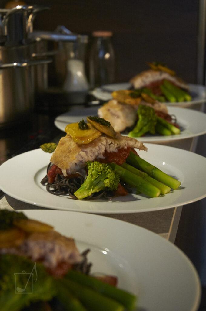 Nudeln aus schwarzen Bohnen mit Tomatensauce, Fisch, gedämpftem, grünem Spargel und Brokkoliröschen und zwei Bratkartoffeln mit Pesto.
